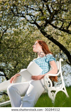 Red hair woman sitting on white bench with book in green meadow in spring