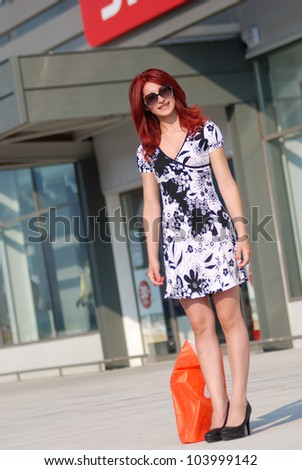 Red hair woman with shopping bag against of store entrance