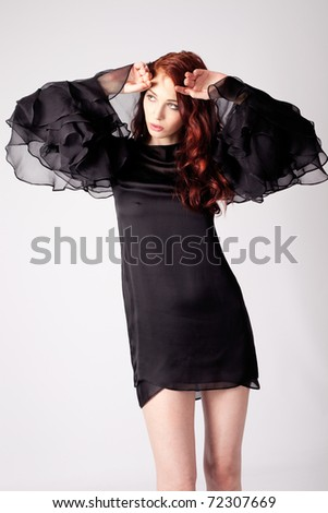red hair womanin elegant black dress, studio shot