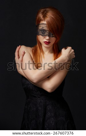 Red-haired beauty with lace mask on eyes - stock photo