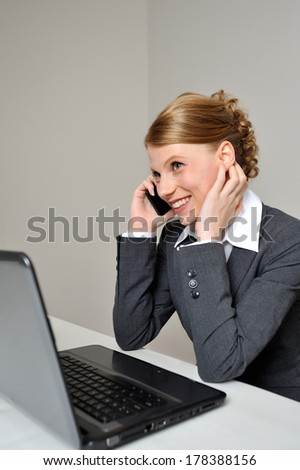 Red haired business woman having a cheerful conversation on the phone. She is at work behind her laptop.