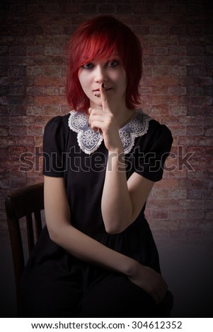 Red-haired girl, approaching darkness, dress with lace collar, piercing on the face, calls for silence, sitting on a chair, blue eyes, vintage image, gloomy picture, vertical photo, brick wall. - stock photo