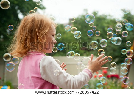 Red-haired girl catches soap bubbles