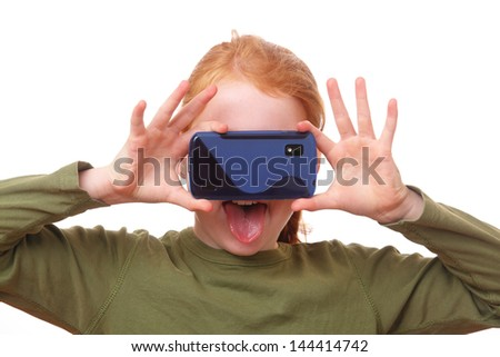 Red haired girl does funny things with her smartphone - stock photo