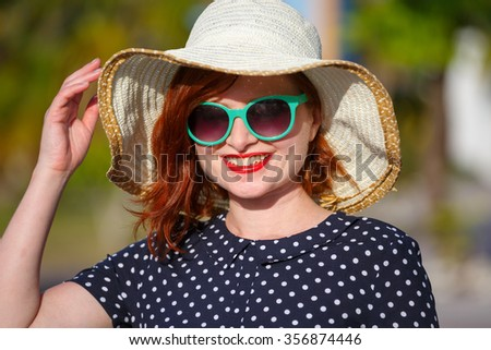 Red-haired girl in a hat and sunglasses on the background of the sea - stock photo