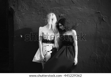 red-haired girl in a red dress and girl with long white hair in a white dress, the two girls standing near a red wall, the wind picks up the dress and her hair, paint was spilled on the dress - stock photo