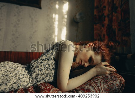Red-haired girl in a white dress in a blue flower  lying on the sofa on colored plaid. He rests his hands on his forehead . In the background, a sewing machine - stock photo
