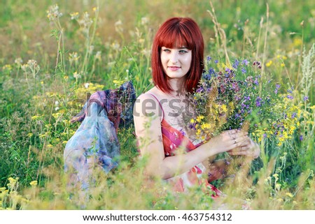 red-haired girl in the field with a bouquet of flowers