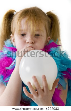 Red-haired girl is blowing a white balloon - stock photo