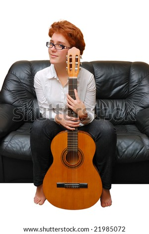 Red-haired girl is sitting on sofa with guitar isolated over white background - stock photo