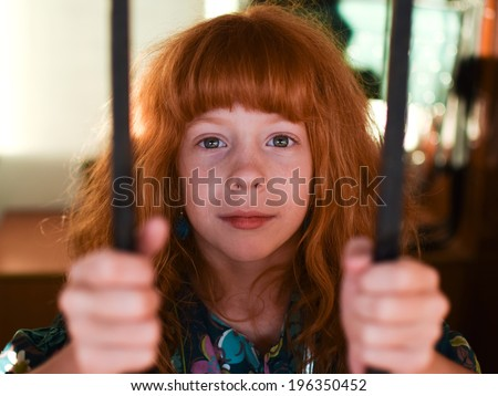 red-haired girl looking in the camera behind the bars on the window - stock photo