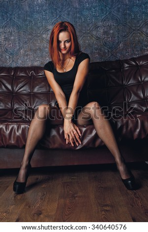 Red-haired girl mulatto sitting on a leather sofa.