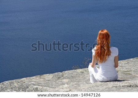 Red-haired girl sitting on a rock and looking over blue water. - stock photo