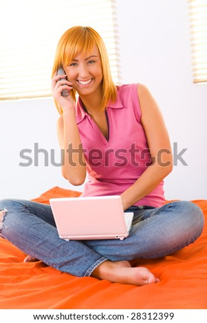 Red-haired girl sitting on bed. She's talking by telephone and doing something on laptop. She's looking at camera. Front view.