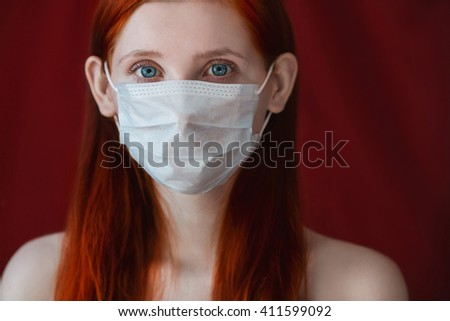 red-haired girl with a medical mask on a red background, woman doctor, woman with intense look, European, flowing hair, eared girl, gauze mask, girl in a protective mask, full-face portrait  - stock photo