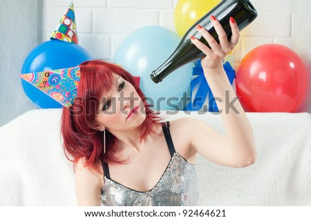 Red-haired party girl with a bad head after the party looking in a bottle - stock photo