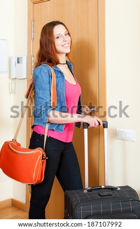 Red haired positive woman comes back home from vacation  - stock photo