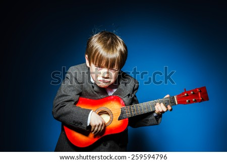 Red-haired preschooler boy with ukalele, isolated on blue, music concept - stock photo