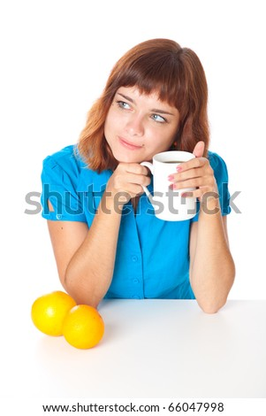 Red-haired teen-girl with cup of coffee and two oranges in hand. Isolated on white