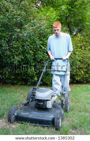 Red-haired teenaged young man mowing the lawn on a bright summer day. - stock photo
