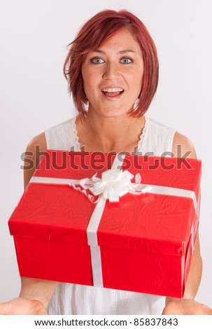 Red haired woman catching a falling red and white present - stock photo