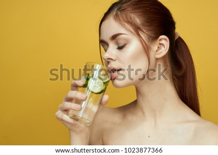 red-haired woman drinks water with cucumber slices, yellow background, health