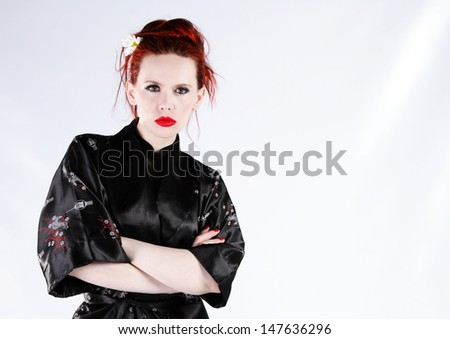 Red haired woman in black kimono - stock photo