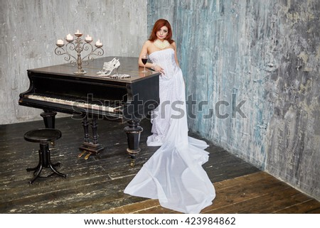 Red-haired woman in white dress stands leaning her elbow on grand piano lid with glass of red wine, burning candles, shoes and necklace in room with ragged walls. - stock photo