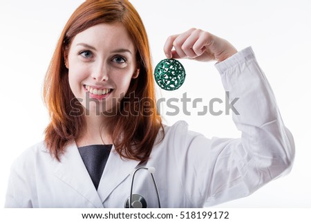 red haired woman is a medical doctor holding a christmas ball to celebrate with patients or to promote an initiative in favor of unlucky people
