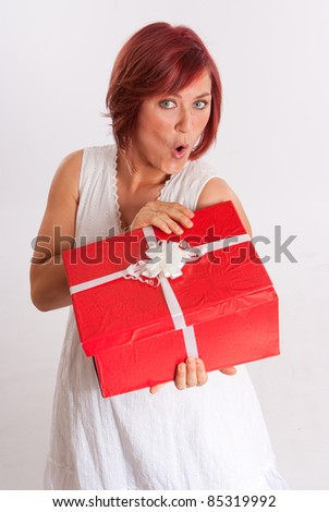 Red haired woman opening a red and white present - stock photo