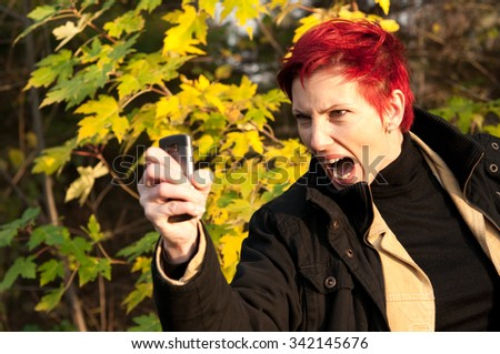 red haired woman showing range against the machine autumn yellow leaves background  - stock photo