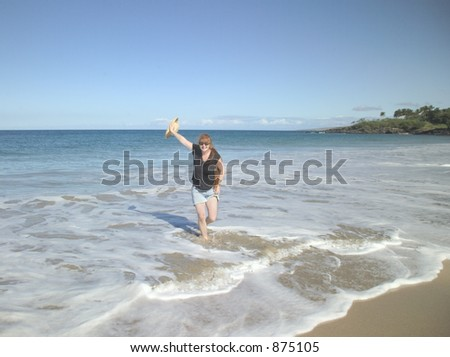 Red haired woman walking in the surf