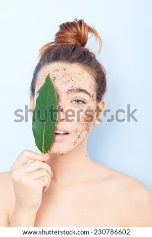 Red-haired woman with a scrub applied and a sheet covering her face - stock photo