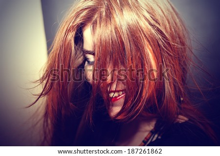 Red-haired young girl with hair fluttering in the wind
