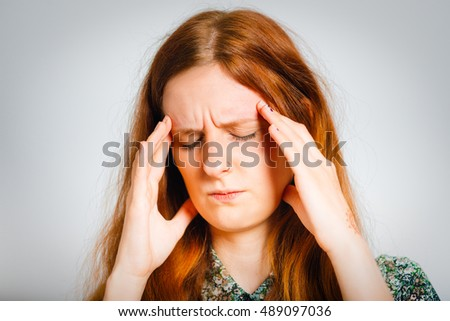 red-haired young woman has a headache