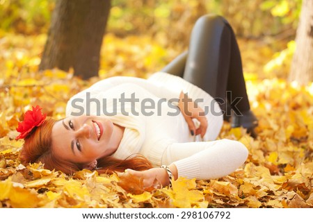 Red-haired young woman lying among red leaves in autumn forest. Outdoor portrait