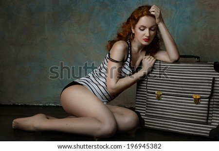 Red haired young woman sitting near a striped suitcase in a striped undershirt dreaming of her vacations - stock photo