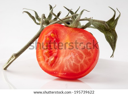 Red half of tomato with green branch - stock photo