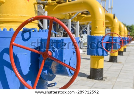 Red handle gate valve with steel pipe on gas compressor station - stock photo