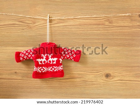 Red handmade sweater on wooden background - stock photo