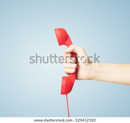 red handset in hand on blue background - stock photo