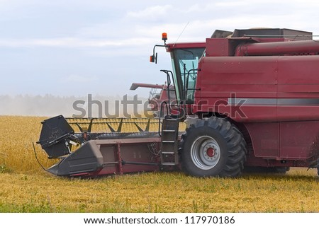 Red Harvester  for harvesting wheat on  background field and sky, Russia.