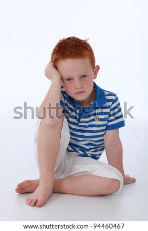 Red head boy wearing blue striped shirt with sad expression on face - stock photo