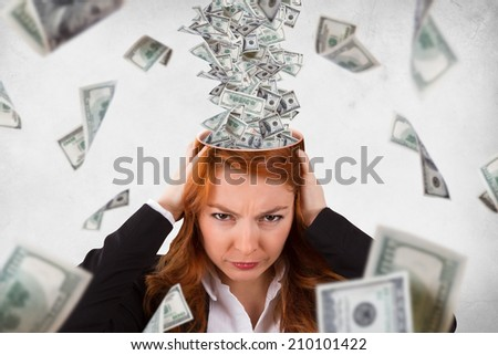 Red head woman holding her head with angry emotion, expression and dollar banknotes instead of brain flowing around, isolated on grunge, white background. - stock photo