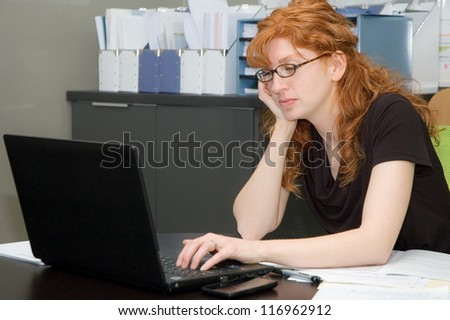 Red head woman working on a laptop in her office. - stock photo