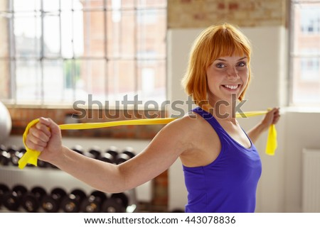 Red headed athlete holds yellow stretch band across her shoulders while exercising in a fitness center near hand weights