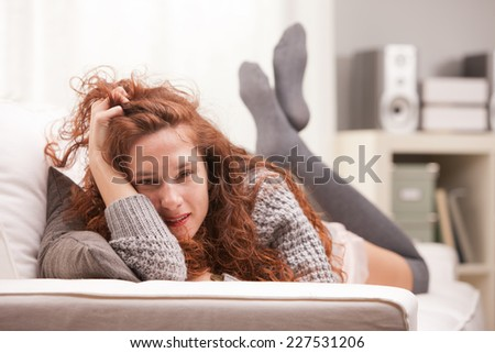 Red Headed very cute girl sexy on her sofa in her living room - stock photo