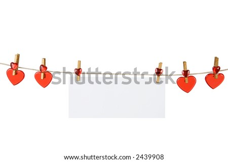 red heart and a slip of paper on a clothesline with gold-colored clothes pin on white background