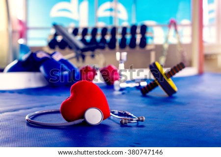 Red heart and a stethoscope in exercise Gym concept. - stock photo