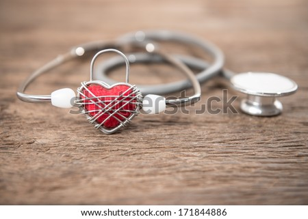 Red heart and a stethoscope on wood background - stock photo